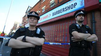 Police officers stand on duty outside the Fade Away barber shop on Princess Road in Moss Side, Manchester, on May 26, 2017, following an early morning raid as their investigations continue into the May 22 terror attack at the Manchester Arena. Britain is hunting for a Libya-linked jihadist network thought to be behind the May 22 bombing at an Ariana Grande concert in Manchester, as US President Donald Trump threatened to prosecute anyone leaking details from the investigation to US media. / AFP PHOTO / Lindsey Parnaby        (Photo credit should read LINDSEY PARNABY/AFP/Getty Images)
