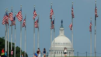 Flags fly at the Washington Monument, as the U.S. Capitol is seen at rear, on Flag Day in Washington, U.S., June 14, 2017. REUTERS/Joshua Roberts