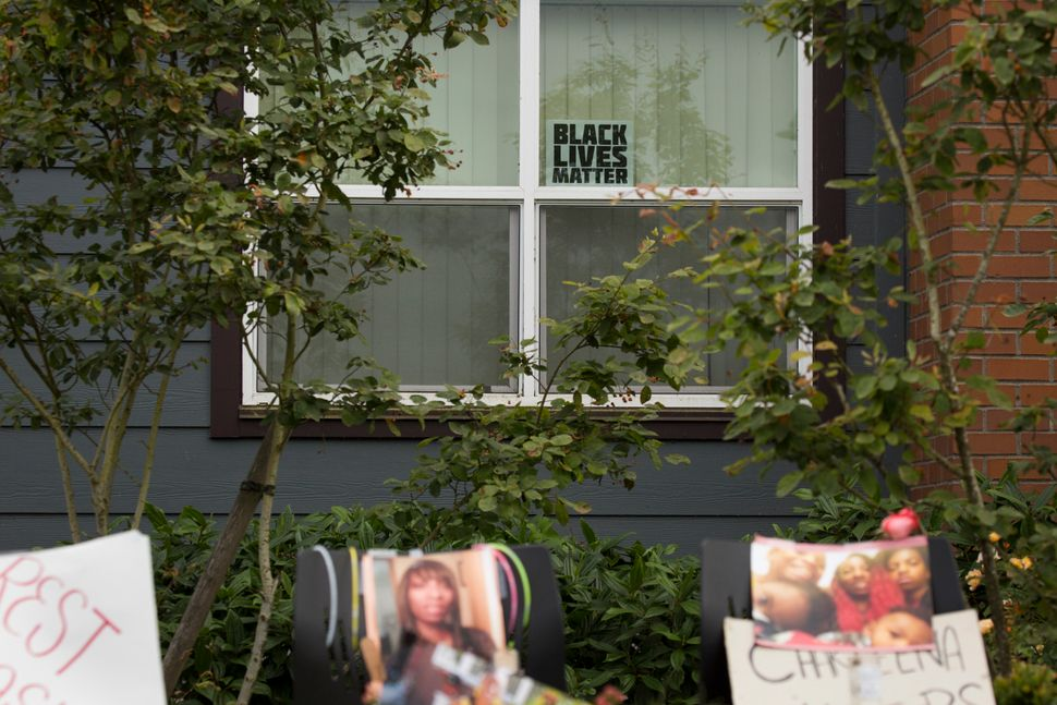 A Black Lives Matter sign sits in a window behind a memorial for Charleena Lyles at the Seattle apartment building where she