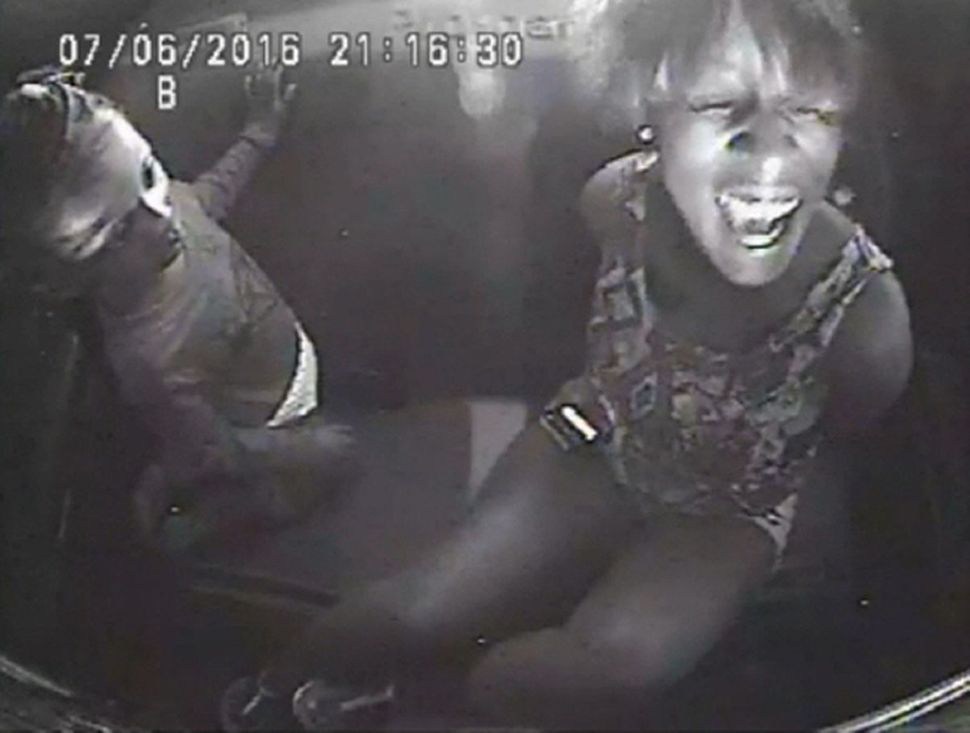 A still image from police video shows Diamond Reynolds crying beside her daughter while handcuffed in the back seat of a poli