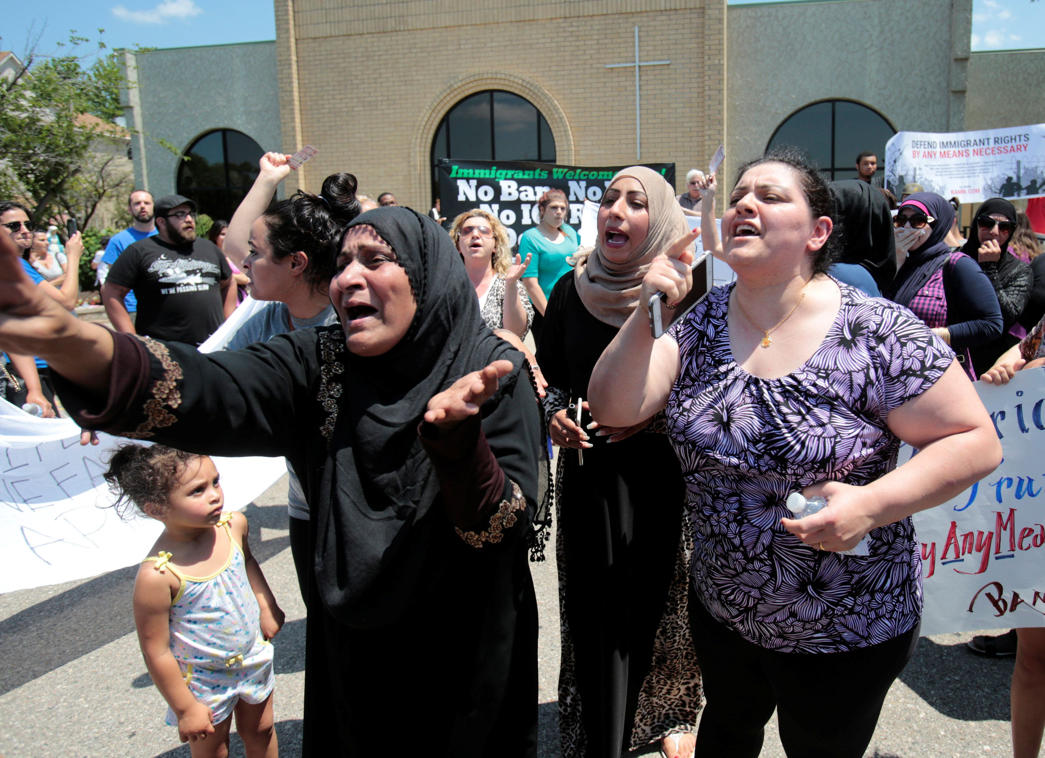 A group of women react as they talk about family members seized on Sunday by Immigration and Customs Enforcement agents during a rally outside the Mother of God Catholic Chaldean church in Southfield, Michigan, U.S., June 12, 2017.   REUTERS/Rebecca Cook