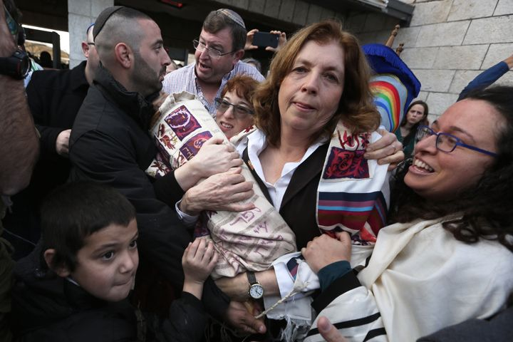 Orthodox Jewish men try to prevent Anat Hoffman (C), the founder and President of the liberal Jewish religious group Women of