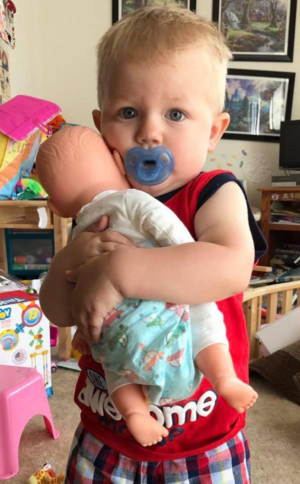 """""""Griffin (1-year-old). He causes destruction everywhere he goes (as seen in the background!) but when he hears this baby cry,"""