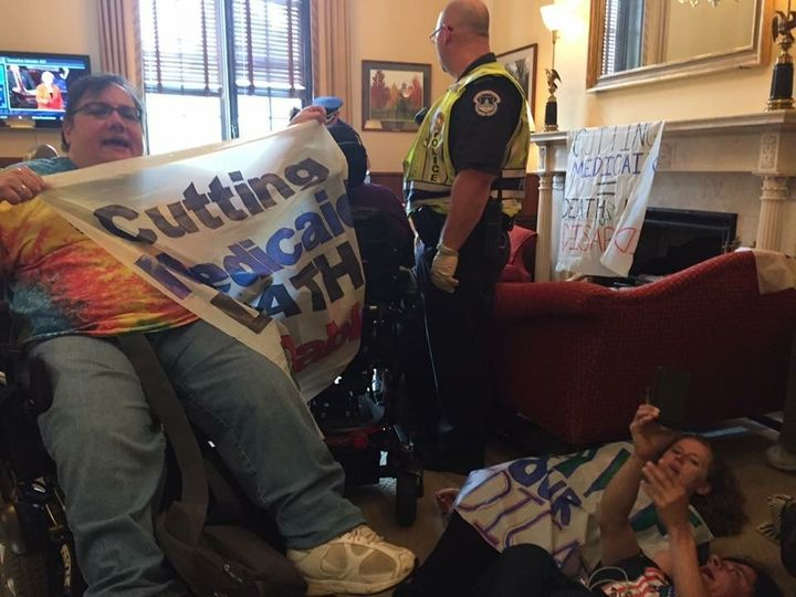 """Susan Stahl in McConnell's office shortly before she was arrested. Her banner reads, """"Cutting Medicaid = Death 4 Disabled."""""""