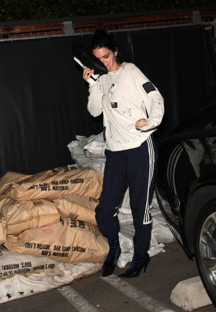 "For a night out in Los Angeles earlier this month, Kendall Jenner donned sweatpants with what Vogue calls ""<a href=""http://www.vogue.com/article/kendall-jenner-kim-kardashian-west-adidas-heels-celebrity-street-style"" target=""_blank"">patent and velvet stiletto boots</a>."""