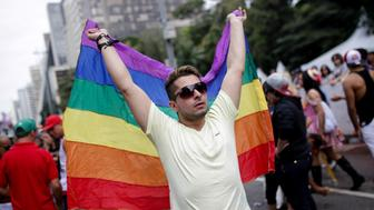 A reveler holds a LGBT's flag during the 19th annual Gay Pride Parade in Sao Paulo, Brazil on June 7, 2015. Every year hundreds of thousands of people gather on Paulista Avenue in Sao Paulo for one of the largest Gay Parades in the world. (Photo by Tiago Mazza Chiaravalloti/NurPhoto) (Photo by NurPhoto/NurPhoto via Getty Images)