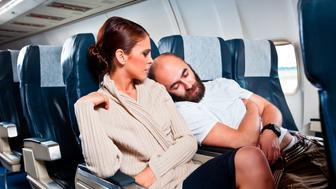 Disgusted woman looking at the sleeping man sitting next to her, who rests his head on her shoulder.