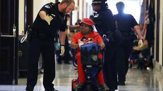 WASHINGTON, DC - JUNE 22:  U.S. Capitol Police remove protesters from in front of the office of Senate Majority Leader Mitch McConnell (R-KY) inside the Russell Senate Office Building on Capitol Hill, on June 22, 2017 in Washington, DC. Members of a group with disabilities were protesting the proposed GOP health care plan that was unveiled today.  (Photo by Mark Wilson/Getty Images)