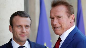 Former California Governor Arnold Schwarzenegger (R) is greeted by French President Emmanuel Macron (L) upon his arrival at the Elysee Palace in Paris, France, June 23, 2017.   REUTERS/Charles Platiau