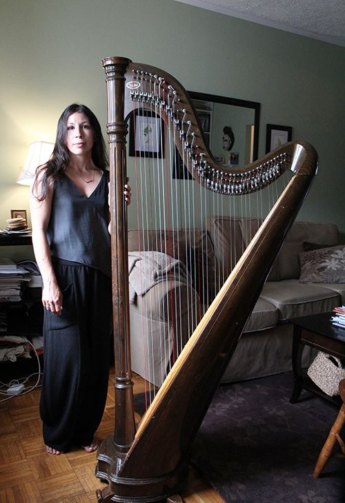 <strong>The 50-pound lever harp towers over Tracey.</strong>