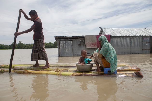 In this August 2016 photo, a family on a raft approaches a boat in a flooded area of Jamalpur,