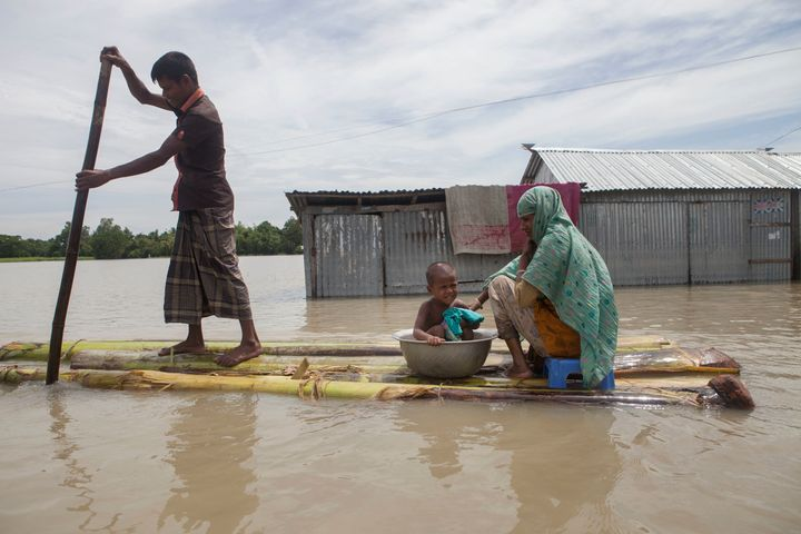 In this August 2016 photo, a family on a raft approaches a boat in a flooded area of Jamalpur, Bangladesh.
