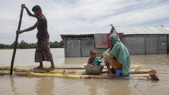 JAMALPUR, MYMENSINGH, BANGLADESH - 2016/08/02: A family on a raft approaches a boat at flood affected area in Jamalpur. According to the Bangladesh Disaster Management Bureau around 1.5 million people have been affected by this year flood. Rivers in the north started to rise in early July and by the 20th of July nearly all of them started to flow over the danger level. It caused floods in 6 districts, namely, Lalmonirhat, Kurigram, Gaibandha, Jamalpur, Sirajganj and Sunamganj initially and inundated crop fields and dwelling areas, washed away standing crops, houses and households assets, livestock and displaced the affected people.Bangladesh is one of the most climate change-vulnerable and disaster-prone countries. The rivers of this country are facing tremendous environmental anomalies. They overflow during the rainy season but shrink in other seasons. Floods in our country are directly or indirectly related to sub-Himalayan countries like India, Bhutan, and Nepal. An understanding should be made to protect the eco-system in the regions to minimize the risks of flash floods, and to share the water resources as per international laws. (Photo by Probal Rashid/LightRocket via Getty Images)