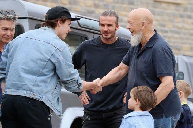 Brooklyn Beckham (2nd L) meets Glastonbury Festival founder Michael Eavis (R) with his father David Beckham