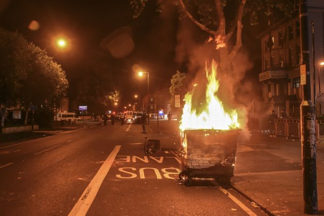 A bin burns near Forest Gate police station on Sunday