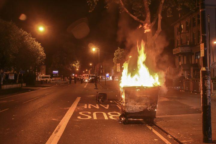 A bin burns near Forest Gate police station on Sunday evening