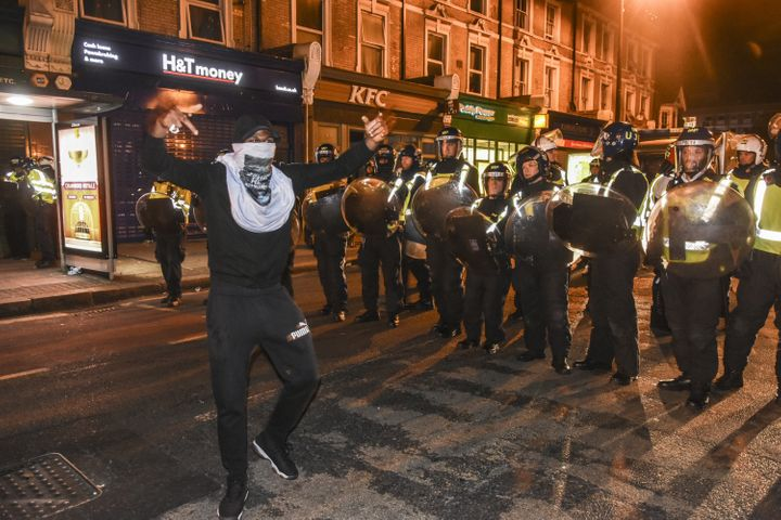 A demonstrator stands in front of riot police