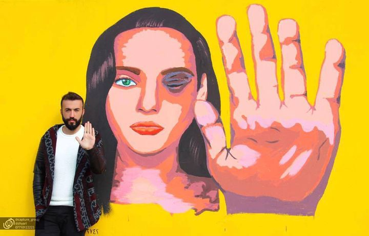 Kurdish LGBT activist Ayaz Shalal with one of his organization's public art projects for gender equality, in Sulaimaniya, Ira