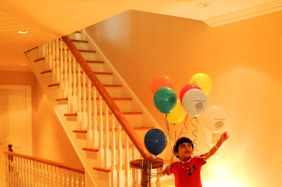 "Yemeni-American Muslim boy Salman Udayni, 5, plays with balloons with the words ""Eid Mubarak"" in celebration of the Eid al-Fi"