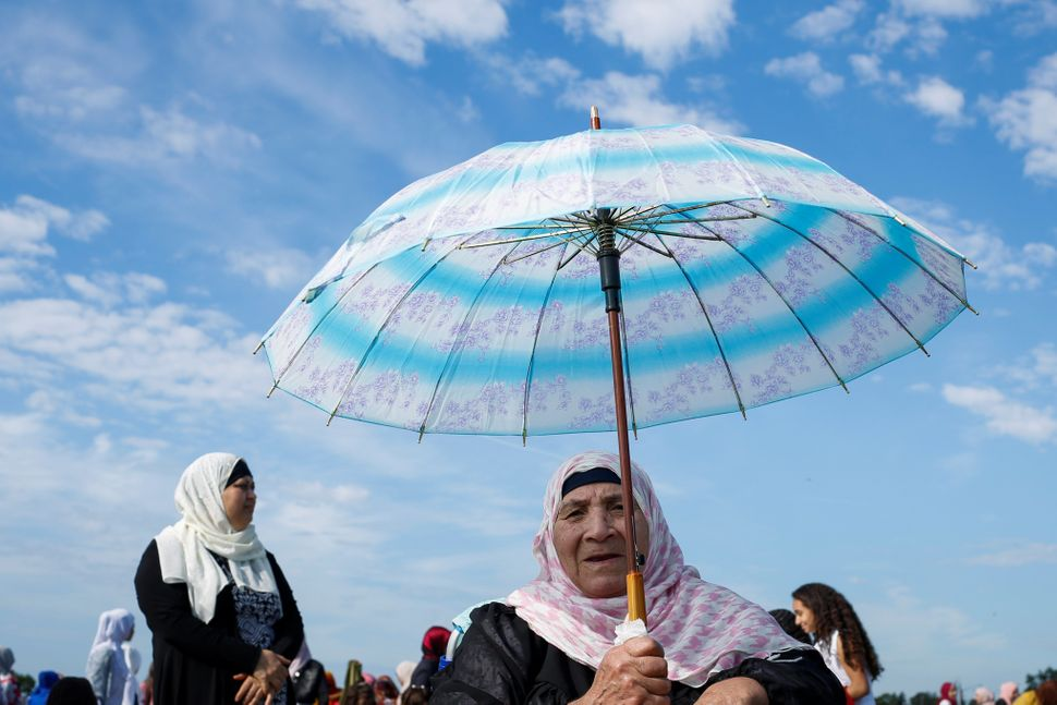 A Muslim woman holds an umbrella as she prepares to take part in Eid al-Fitr prayers in Staten Island, New York, U.S., June 2