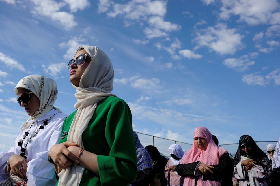 Yemeni-American Muslim sisters Hajar Udayni (L) and Sara Udayni Udayni take part in Eid al-Fitr prayers in Brooklyn, New York