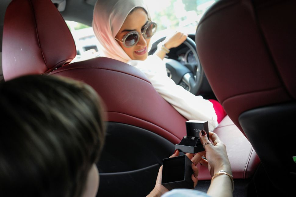 Yemeni-American Muslim Iman Udayni turns to look from the driver's seat at a pair of earrings her daughter Hajar Udayni recei
