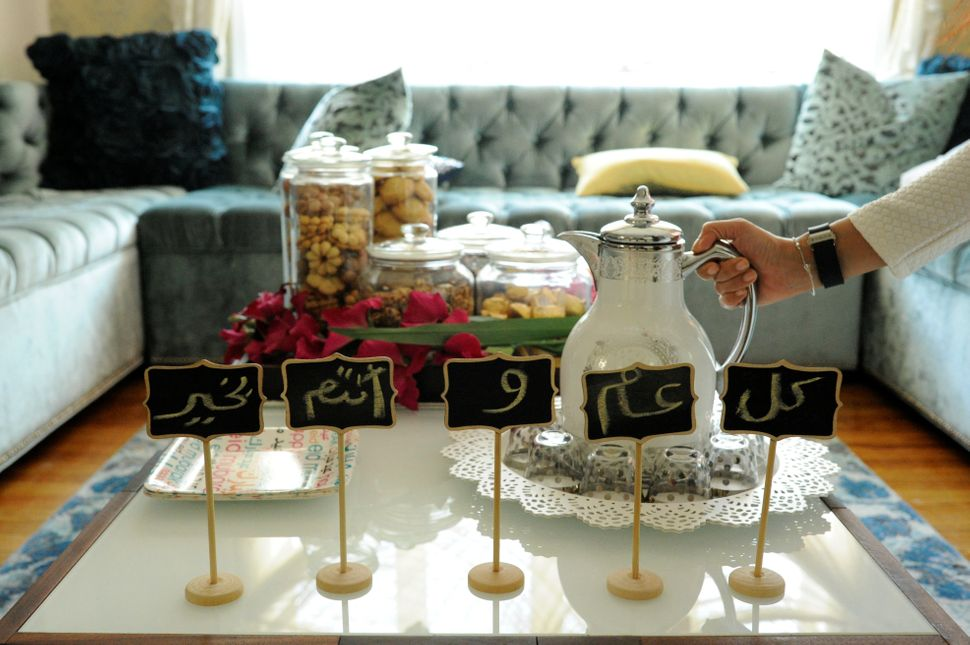 Eid greetings, which wish wellness for the year, make up decorations around sweets and Arabic coffee at the home of the Yemen