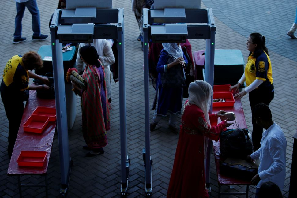 Muslim women pass through security as Muslims gather for the celebration of the Eid al-Fitr holiday, the end of the holy mont