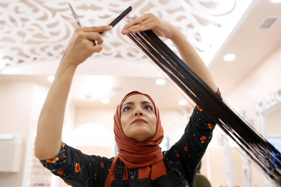 Huda Quhshi, owner and cosmetologist at the Le'Jemalik Salon and Boutique, cuts the hair of a Muslim woman ahead of the Eid a