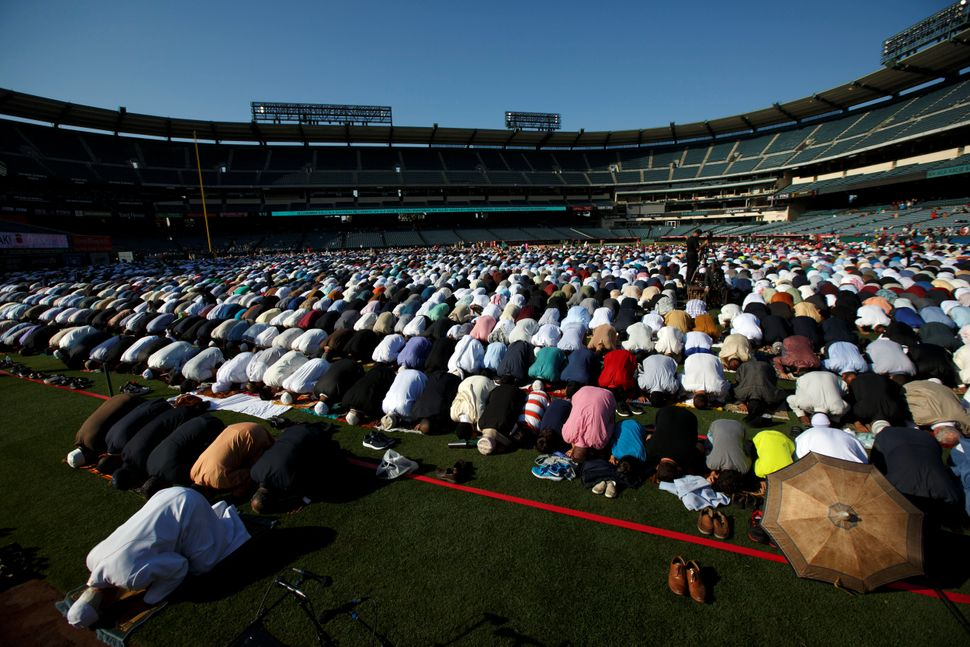 Dr. Muzammil Siddiqi of the Islamic Society of Orange County (L) prays with Muslims gathered for the celebration of the Eid a