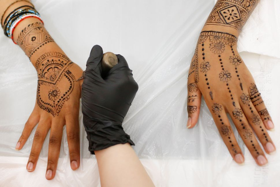 Henna is applied to the hands and arms of a Muslim female customer at the Le'Jemalik Salon and Boutique ahead of the Eid al-F