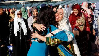 Muslim women hug as they gather for the celebration of the Eid al-Fitr holiday, the end of the holy month of Ramadan at Angel Stadium of Anaheim in Anaheim, California, U.S., June 25, 2017. REUTERS/Patrick T. Fallon