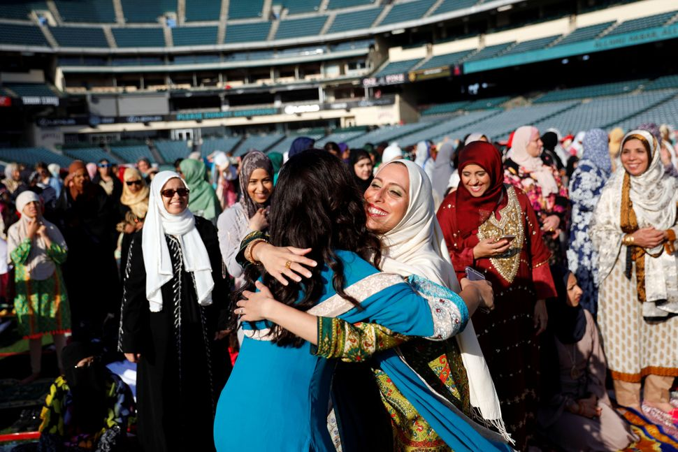 Muslim women hug as they gather for the celebration of the Eid al-Fitr holiday, the end of the holy month of Ramadan at Angel