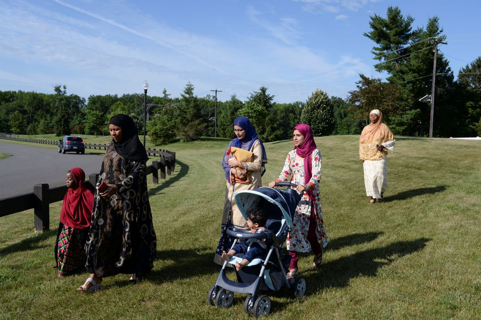 Muslim women walk to a nearby park to take part in Eid al-Fitr prayers in South Brunswick Township, New Jersey, U.S., on June