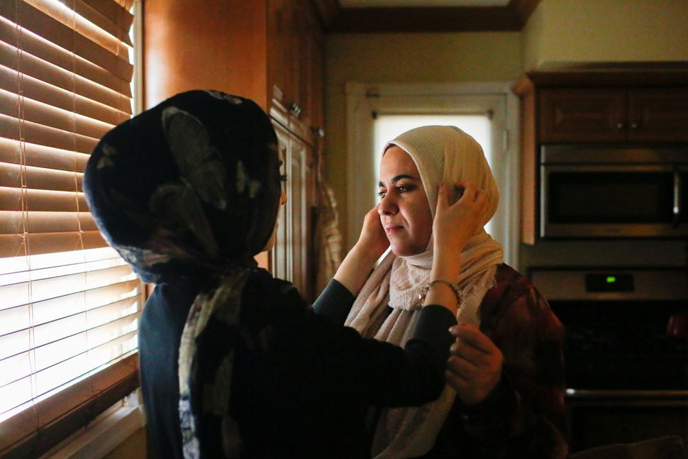 Nevien Shehadeh, 19, a Palestinian American, adjusts the head scarf of her mother Wisal before they depart their home to take