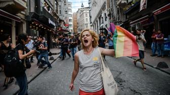 TOPSHOT - A LGBT member waves a rainbow flag during a rally staged by the LGBT community on Istiklal avenue in Istanbul on June 26, 2016. Riot police fired tear gas and rubber bullets to disperse protesters defying a ban on the city's Gay Pride parade. Authorities in Turkey's biggest city had banned the annual parade earlier this month citing security reasons, sparking anger from gay rights activists.  / AFP / OZAN KOSE        (Photo credit should read OZAN KOSE/AFP/Getty Images)