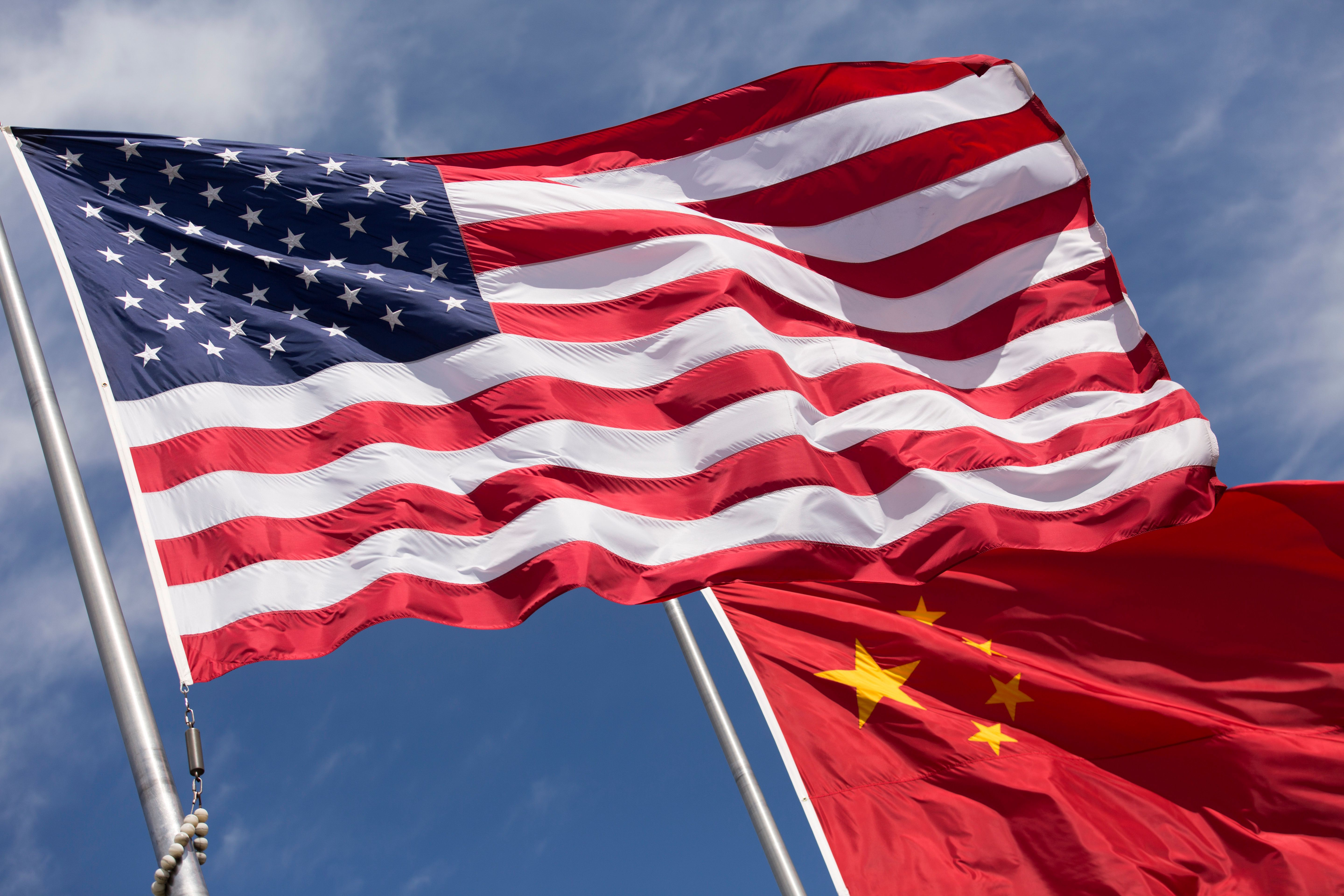 Symbolic of Sino-American relations, the flag of the United States of America and the flag of the Republic of China fly together on flag poles next to each other on a sunny, windy day.
