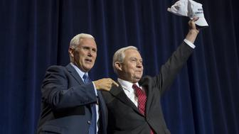 Mike Pence, 2016 Republican vice presidential nominee, left, and Senator Jeff Sessions, a Republican from Alabama, gesture during a campaign event for Donald Trump, 2016 Republican presidential nominee, not pictured, in Phoenix, Arizona, U.S., on Wednesday, Aug. 31, 2016. Trump returned to form in Phoenix Wednesday night with a nativist immigration plan definitively ruling out legal status for undocumented immigrants, as well as proposing to build a wall on the southern border of the United States and forcing Mexico to cover the cost. Photographer: David Paul Morris/Bloomberg via Getty Images
