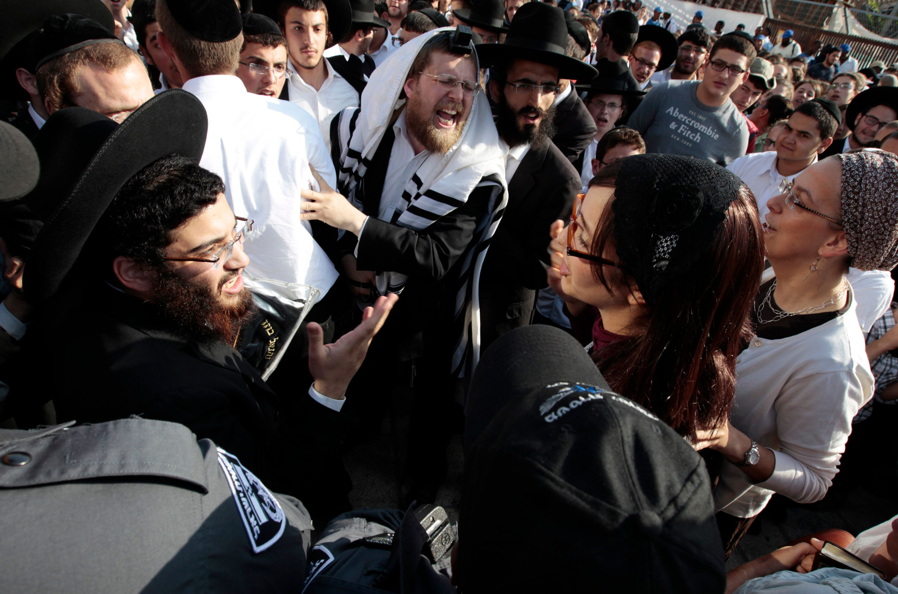 Ultra-Orthodox Jewish men shout at Jewish female activists, members of the Women of the Wall group, during a monthly prayer s