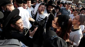 Jewish women, members of Women for the Wall, (R) an organisation calling for the keeping of traditions practiced for thousands of years at the Western Wall, walk near ultra-Orthodox Jewish men as they shout at other Jewish female activists, members of the Women of the Wall group, (not pictured) during a monthly prayer session at a spot a short distance from Western Wall plaza in Jerusalem's Old City July 8, 2013. Several thousand ultra-Orthodox protesters effectively blocked members of the Women of the Wall, campaigning for equal worship rights at the Western Wall from holding a monthly prayer session on Monday at the holy site. REUTERS/Ammar Awad (JERUSALEM - Tags: RELIGION CIVIL UNREST)
