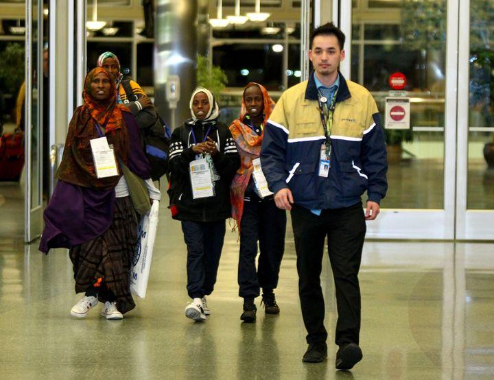 Safiya Hassan, Dahaba Matan, Farduwsa Matan, and Nima Matan, refugees from Somalia, are escorted by a United Airlines represe