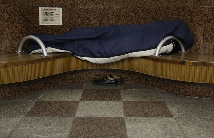 A homeless man snuggles in a sleeping bag on a bench at an underground passage near Sendai Station, December 2013.