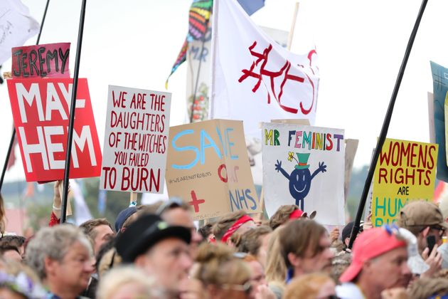 Crowds hold signs as they are excited by Jeremy Corbyn as he speaks on the Pyramid stage at Glastonbury...