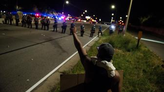 ST. PAUL, MN - JULY 09: A protestor raises his fist on shut down highway I-94 on July 9, 2016 in St. Paul, Minnesota. Protests and marches have occurred every day since the police killing of Philando Castile on June 6, 2016 in Falcon Heights, Minnesota. (Photo by Stephen Maturen/Getty Images)