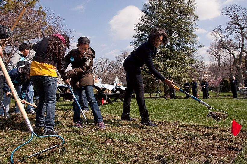 Former First Lady Michelle Obama working with kids from Washington's Bancroft Elementary School to break ground for a White H