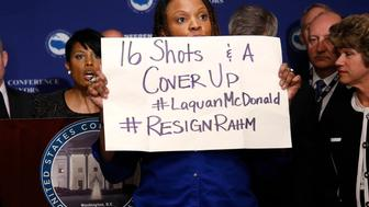 A protester against Chicago Mayor Rahm Emanuel (not pictured) stands in front of U.S. Conference of Mayors President Baltimore Mayor Stephanie Rawlings-Blake (at podium) at the opening press conference of the U.S. Conference of Mayors in Washington January 20, 2016. The sign the protester holds refers to the controversy surrounding the October 2014 shooting of black teenager Laquan McDonald by a white Chicago police officer.  REUTERS/Gary Cameron