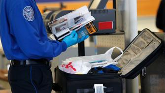A Transportation Security Administration (TSA) officer inspects items from a piece of luggage at Los Angeles International Airport in Los Angeles, California March 4, 2013. Secretary of Homeland Security Janet Napolitano on Monday cautioned airline passengers to get to the airport extra early because U.S. spending cuts have already led to long lines at some security checkpoints, and said the coming furloughs will only make the situation worse. REUTERS/Mario Anzuoni  (UNITED STATES - Tags: TRANSPORT BUSINESS)