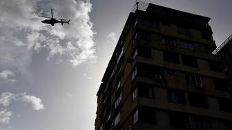 CARACAS, VENEZUELA - JUNE 26: A police helicopter is seen flying during a protest demanding Venezulan President Nicolas Maduro's resignation and new elections in Caracas on June 26, 2017 A political and economic crisis in the oil-producing country has spawned often violent demonstrations by protesters demanding Maduro's resignation and new elections. The unrest has left 75 people dead since April 1. (Photo by Carlos Becerra/Anadolu Agency/Getty Images)