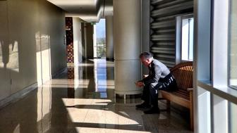 Former Arizona Superintendent of Schools John Huppenthal checks his phone in the federal courthouse in Tucson on June 26 2017