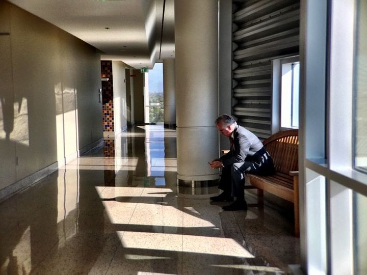 Former Arizona Superintendent of Schools John Huppenthal checks his phone in the federal courthouse in Tucson on June 26, 201